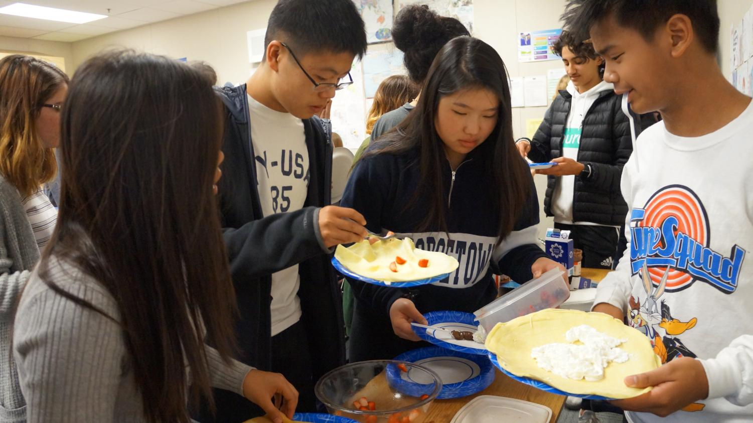 Students enjoy crepes at a French Club meeting.