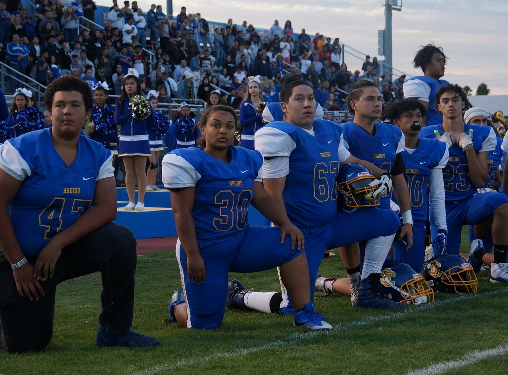 Players use their platform to kneel.  (Pictured left to right: Tavon Ross, Racquel Blassingame, Nick Martinez, Eduardo Mora, Jericaih Papagayo, Seth Everett)