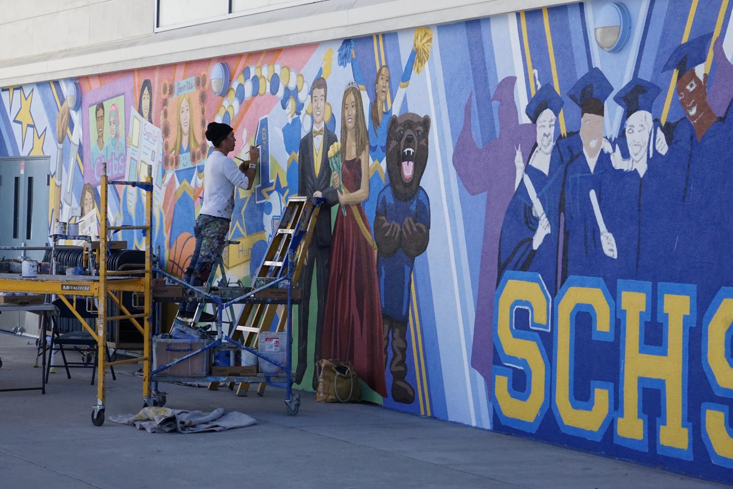 Muralist Paul Gonzalez works hard to complete the piece.
