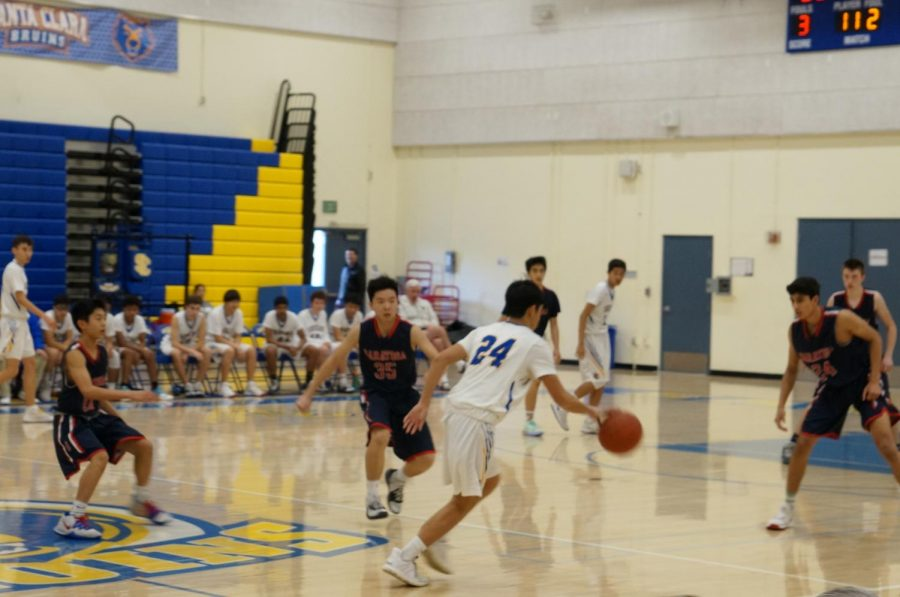 Freshman Ethan Lam dribbles down the court.